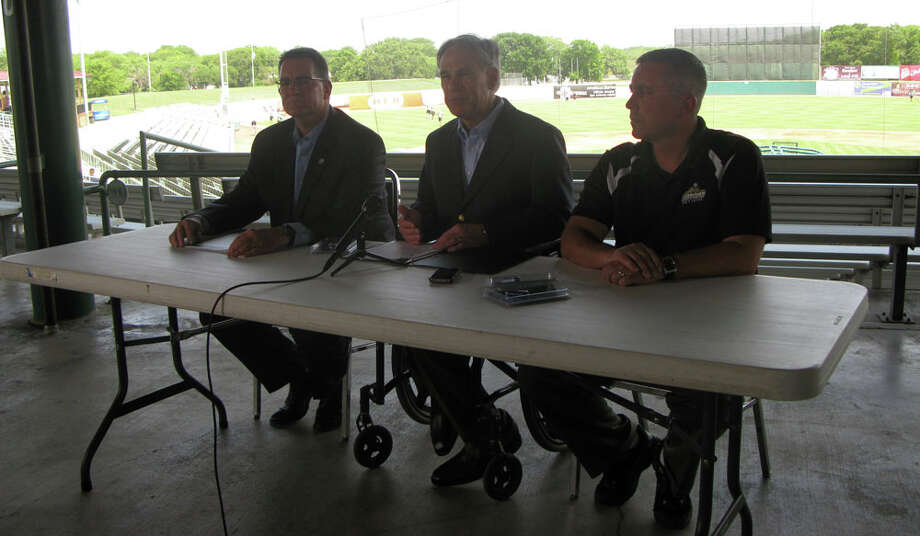 Attorney General Greg Abbott addresses media hours before his office donated child protection flash drives to the first 1,000 fans at a Missions baseball game Friday night. He is flanked by David Boatright (at left), executive director of the Texas office of the National Center for Missing & Exploited children (right), and San Antonio Missions General Manager David Gasaway.
