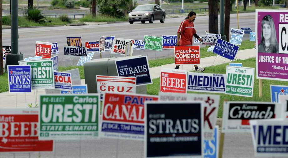 A man walks through a sea of election signs at an early voting polling site on Wednesday in San Antonio. Election day in Texas is today, May 29. Photo: AP
