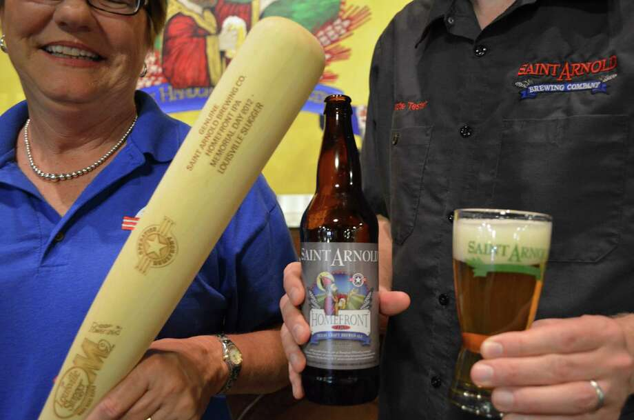 Jennifer Cernoch, left, president of Operation Homefront of Texas, and Saint Arnold Brewing Co. founder Brock Wagner with a bottle of Homefront India Pale Ale to support the organization and Texas military families and a Louisville Slugger bat that it was aged in. Photo: Houston Chronicle