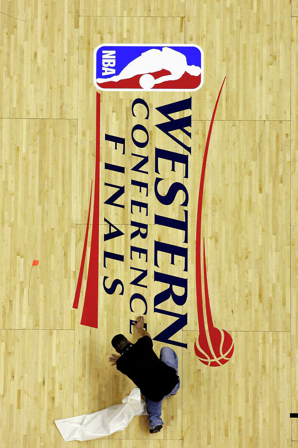 AT&T Center employee Cecilio Santibanez applies the Western Conference Finals logo to the court Friday May 25, 2012 at the AT&T Center. Photo: Edward A. Ornelas, San Antonio Express-News / © 2012 San Antonio Express-News