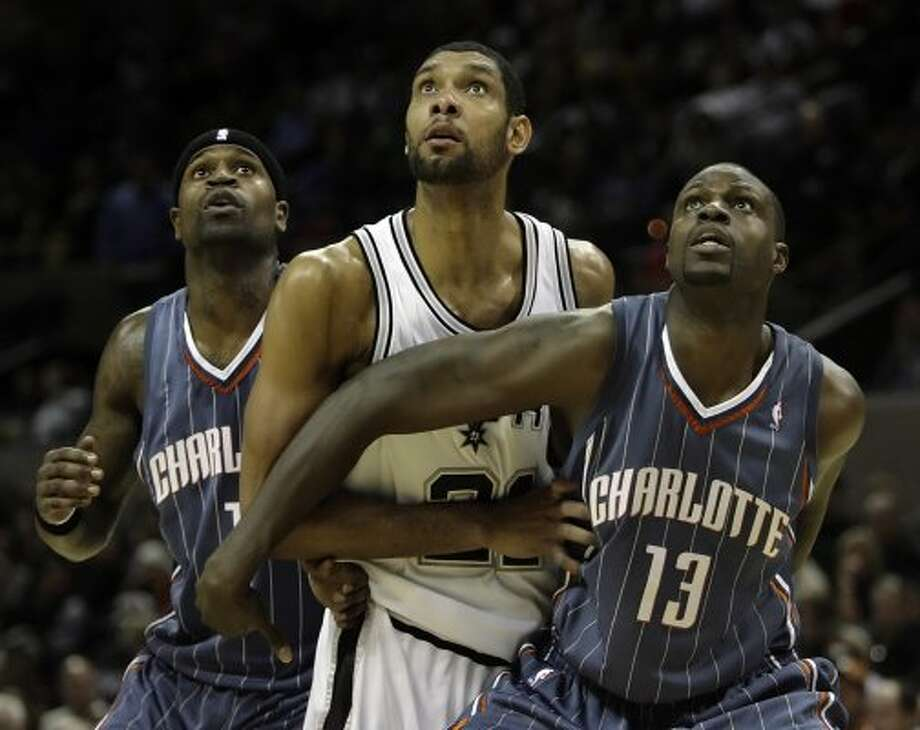 Spurs' Tim Duncan (center) is surrounded by former teammates and current Charlotte Bobcats' Stephen Jackson (left) and Nazr Mohammed in the second half at the AT&T Center on Friday, Dec. 11, 2009. Kin Man Hui/kmhui@express-news.net (KIN MAN HUI / San Antonio Express-News)