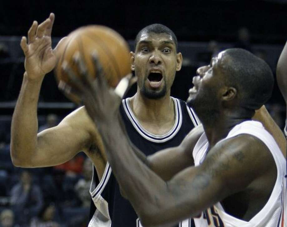 Spurs' Tim Duncan, back, reacts as Bobcats' Nazr Mohammed, front, prepares to shoot in the first half of an NBA basketball game in Charlotte, N.C., Friday, Jan. 15, 2010. (AP Photo/Chuck Burton) (AP)