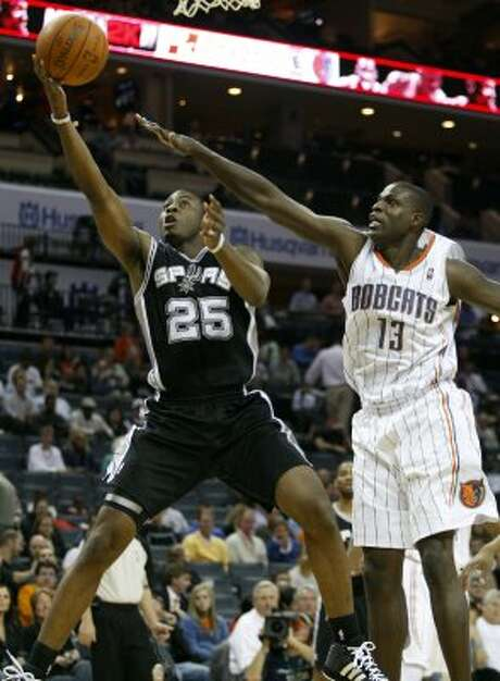 Spurs guard James Anderson, left, drives past Bobcats center Nazr Mohammed in the first half of an NBA basketball game Monday, Nov. 8, 2010 in Charlotte, N.C. (AP Photo/Nell Redmond) (AP)