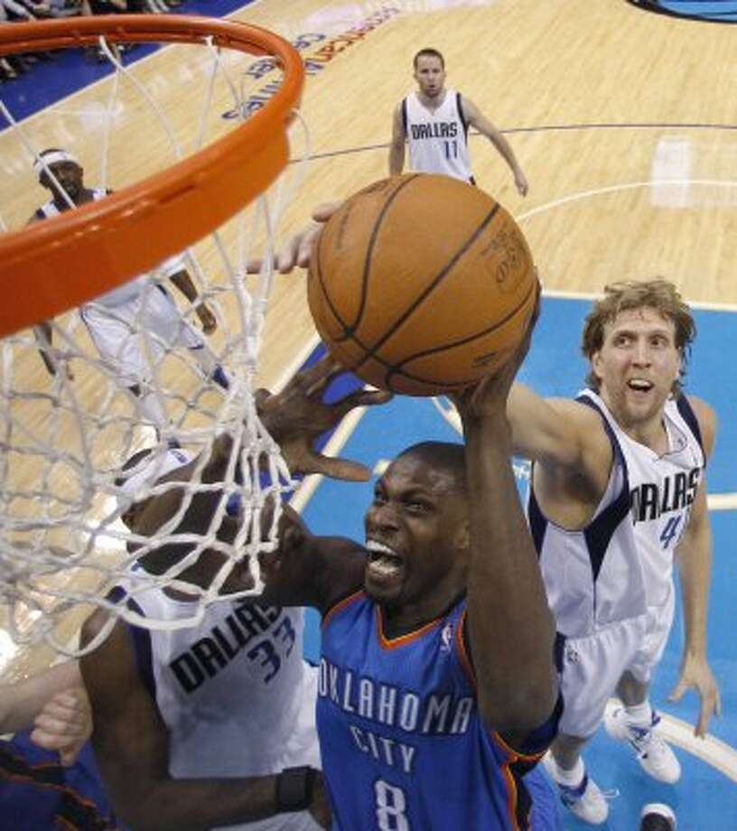 Thunder center Nazr Mohammed (8) drives to the basket against Mavericks center Brendan Haywood (33) and forward Dirk Nowitzki (41) during the first half of Game 1 of the NBA basketball Western Conference finals Tuesday, May 17, 2011, in Dallas. (AP Photo/Eric Gay) (ASSOCIATED PRESS)