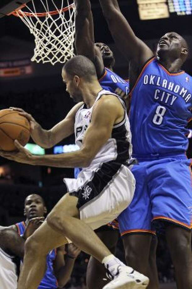 Spurs guard Tony Parker gets Nazr Mohammed (8) and  a teammate hanging in there as he fakes to the basket as the San Antonio Spurs play the Oklahoma City Thunder at the AT&T Center  on February 4, 2012 Tom Reel/ San Antonio Express-News (TOM REEL / San Antonio Express-News)