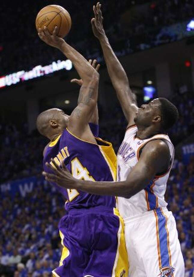 Lakers guard Kobe Bryant, left, shoots as Thunder center Nazr Mohammed, right, defends, in the third quarter of Game 1 in the second round of the NBA basketball playoffs, in Oklahoma City, Monday, May 14, 2012. Oklahoma City won 119-90.(AP Photo/Sue Ogrocki) (AP)
