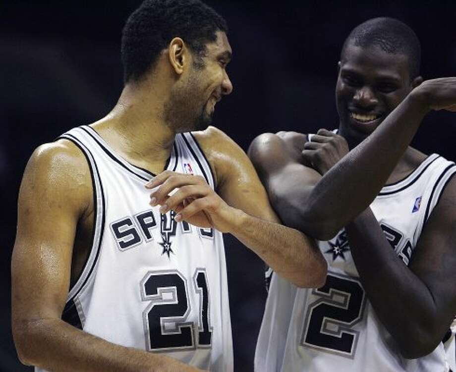 Tim Duncan and Nazr Mohammed share a laugh during a timeout in the second half Tuesday, February 21, 2006 at the AT&T Center. BAHRAM MARK SOBHANI/STAFF (BAHRAM MARK SOBHANI / SAN ANTONIO EXPRESS NEWS)