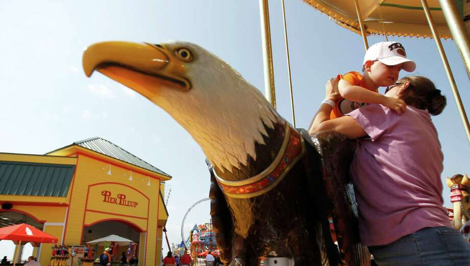 Mason Vinsant, 3, of Tomball gets help getting of an eagle by his mother Britany, on the carousel at the new Pleasure Pier. Photo: Karen Warren, Houston Chronicle / © 2012  Houston Chronicle