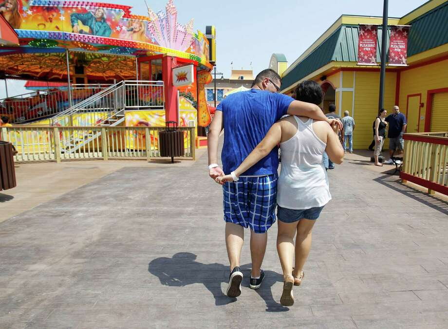 Miguel Lopez, 18, hugs his girlfriend Mariana Martinez, 17, both of Port Arthur, while walking along the new Pleasure Pier. Photo: Karen Warren, Houston Chronicle / © 2012  Houston Chronicle