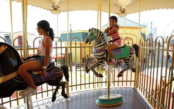 Riding the carousel at the new Pleasure Pier. Photo: Karen Warren, Houston Chronicle / © 2012  Houston Chronicle