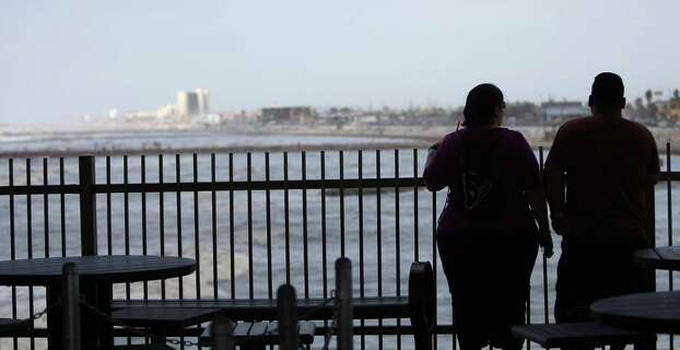 A couple looks over the fence at the Gulf from the new Pleasure Pier. Photo: Karen Warren, Houston Chronicle / © 2012  Houston Chronicle