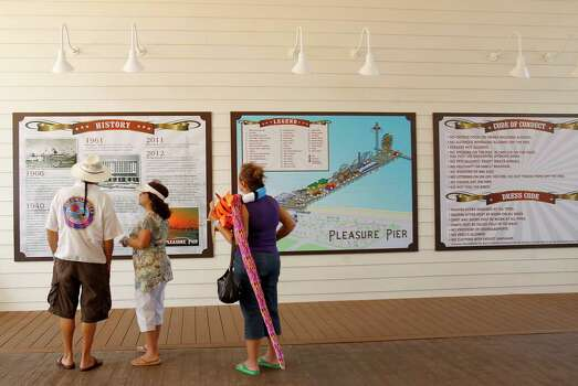 Visitors to the new Pleasure Pier read the site's history. Undated photo. Photo: Karen Warren, Houston Chronicle / © 2012  Houston Chronicle