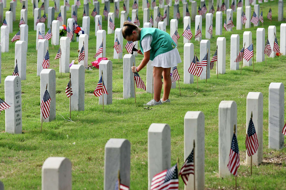 Girl Scout Taylor Thorpe, 9, places an American flag on a grave for Memorial Day at Fort Sam Houston National Cemetery for Friday May 25, 2012.