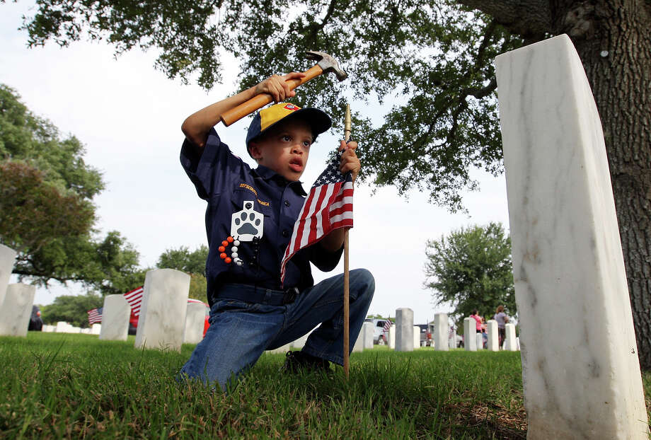 Cub Scout Diego Leal, 6, places an American flag on a grave at Fort Sam Houston National Cemetery Friday May 25, 2012.  The local Memorial Day Program is held annually held to remember and honor all military members who have served or are currently serving in the military. The event is scheduled for 9:30 a.m. at the new assembly area located on the east side of Ft. Sam Houston National Cemetery. Larry Romo, director of the Selective Service System and who is from San Antonio, will give the keynote address. Photo: Edward A. Ornelas, San Antonio Express-News / © 2012 San Antonio Express-News