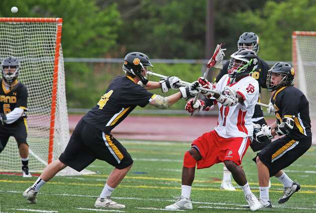 Fairfield Prep's Austin Sims fights for position against Daniel Hand High School defenders in the SCC Championship lacrosse game on Friday May 24, 2012 in Branford, Conn. Photo: Mike Ross / Connecticut Post Freelance