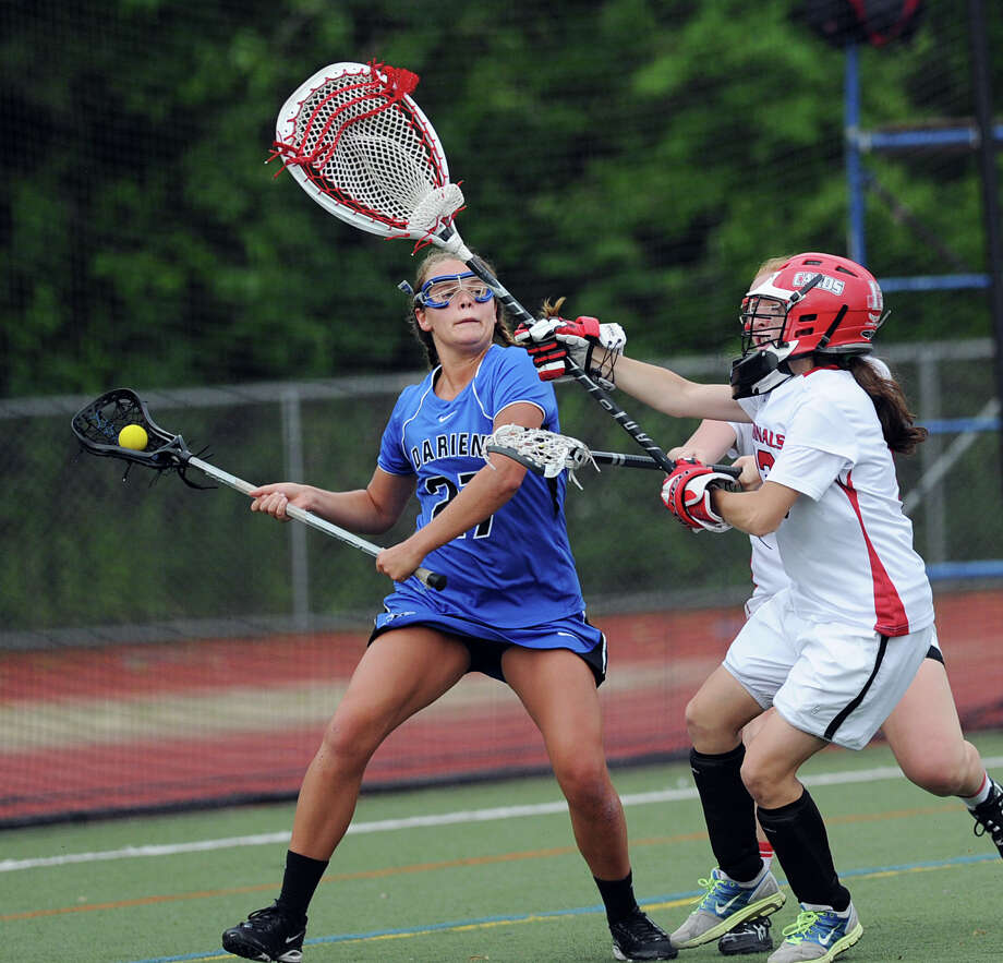 At left, Taylor Hardison # 27 of Darien passes while being covered by Greenwich golaie Hannah Jeffrey during the FCIAC girls lacrosse finals between Greenwich High School and Darien High School at Brien McMahon High School in Norwalk, Friday, May 25, 2012. Darien won the championship over Greenwich 17-14. Photo: Bob Luckey / Greenwich Time