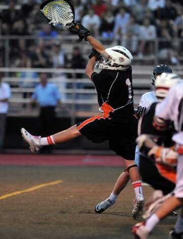 Ridgefield goalie Adam Winne jumps to attempt to block a New Canaan goal during Friday's FCIAC boys lacrosse championship game at Brien McMahon High School in Norwalk on May 25, 2012. Photo: Lindsay Niegelberg / Stamford Advocate