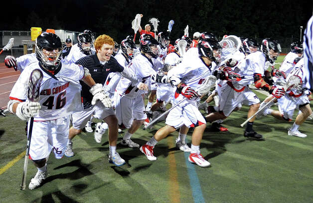 The New Canaan lacrosse team rushes the field after coming from behind to win against Ridgefield in Friday's FCIAC boys lacrosse championship game at Brien McMahon High School in Norwalk on May 25, 2012. Photo: Lindsay Niegelberg / Stamford Advocate