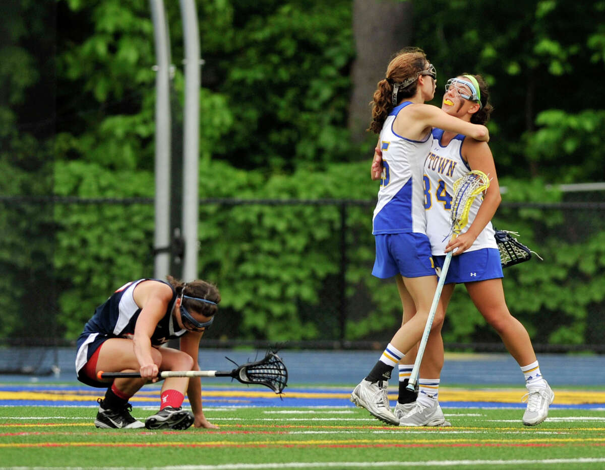 New Fairfield's Carly Hopkins gets back on her feet as Newtown's Erin Kenning and Meredith Bridges celebrate a goal during their Division I SWC championship game at Newtown High School on Friday, May 25, 2012. Newtown won 18-13.