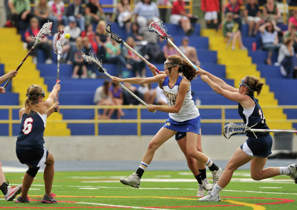 Newtown's Erin Kenning shoots and scores while under pressure from New Fairfield's Casey Jagemann, left, and Tara Donovan during their Division I SWC championship game at Newtown High School on Friday, May 25, 2012. Newtown won 18-13.