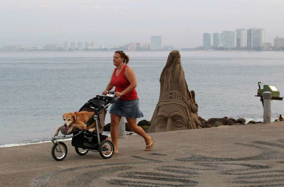 A woman pushes her dog in a baby stroller along the beach in the resort city of Puerto Vallarta, Mexico, Friday, May 25, 2012. Hurricane Bud lost a little of its sting early Friday, but remained a potent Category 2 storm as it headed toward a string of laid-back beach resorts and small mountain villages on Mexico?s Pacific coast south of Puerto Vallarta.  (AP Photo/Bruno Gonzalez) Photo: Bruno Gonzalez / AP