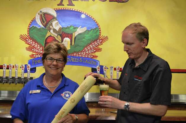 Jennifer Cernoch, president of Operation Homefront of Texas, and Saint Arnold Brewing Co. founder Brock Wagner display a baseball bat used to age beer for the Hops for Heroes program. Photo: Ronnie Crocker / HC