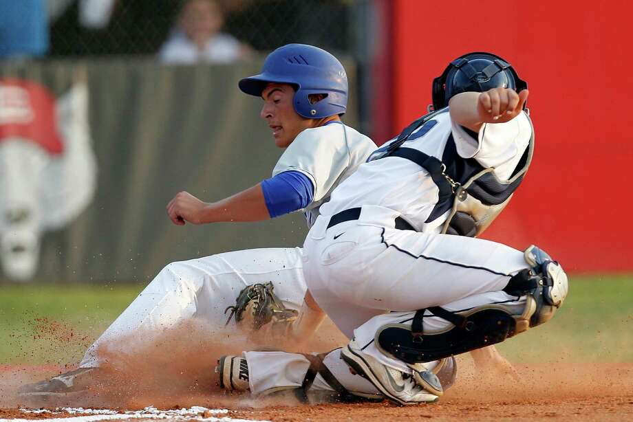 Lamar Consolidated catcher Clay Campbell right, tags out Barbers Hill's Blake Bonnin left, at home plate in the second inning, but the Eagles eked out a 2-1 win. Photo: James Nielsen / © Houston Chronicle 2012