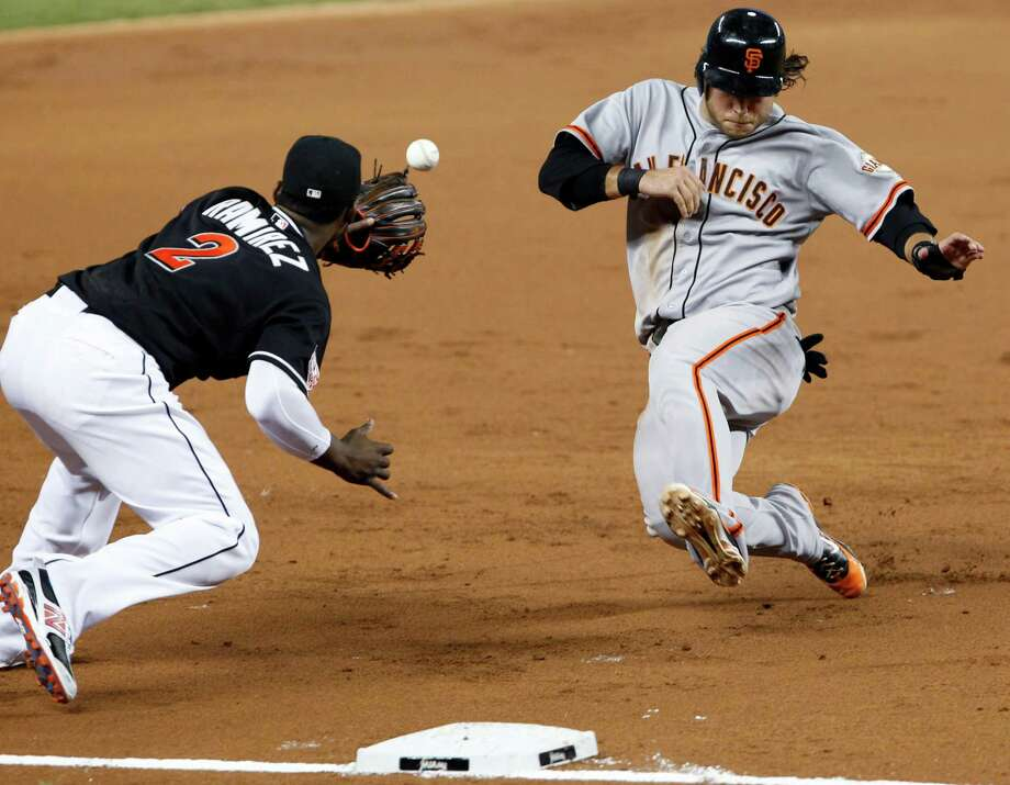 Miami's Hanley Ramirez, left, prepares to tag out the Giants' Brandon Crawford at third base to end the third inning in the Marlins' 7-6 win Friday night. Photo: Wilfredo Lee / AP