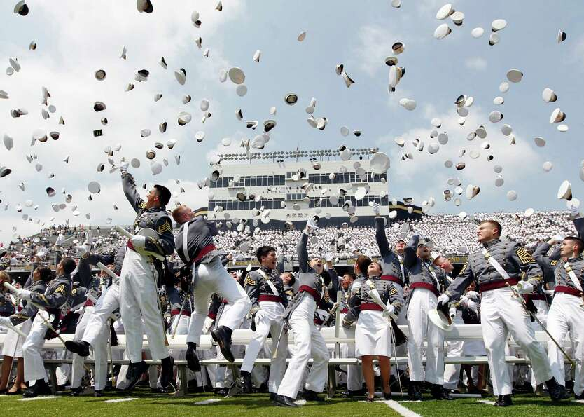 Cadets throw their hats in the air to conclude a graduation and commissioning ceremony at the U.S. M
