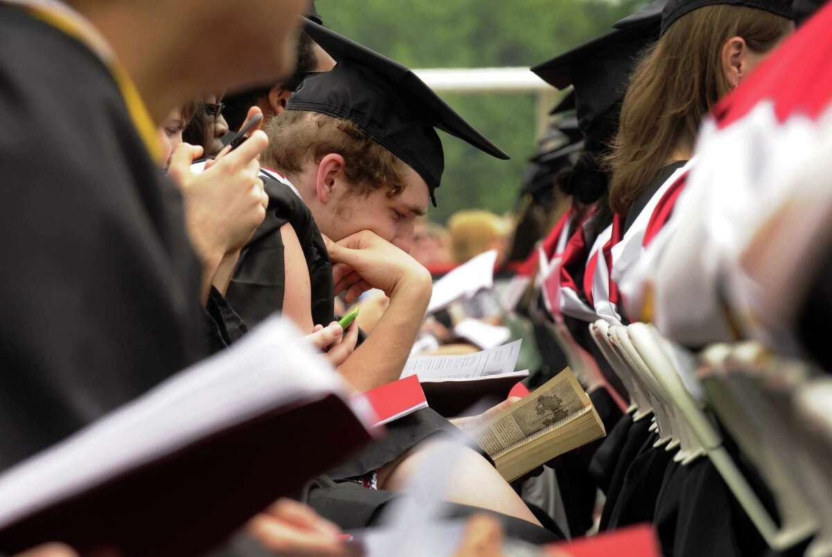 A graduate, center, catches up on his reading during Rensselaer Polytechnic Institute's 206th Commencement in Troy N.Y. Saturday May 26, 2012. (Michael P. Farrell/Times Union)
