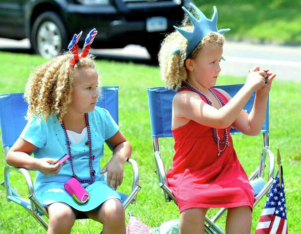 Twin sisters Madelyn, left, and Josephine Kieras, 6, watch the Redding Memorial Day Parade Saturday, May 26, 2012. Photo: Michael Duffy