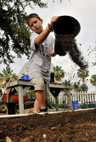 Matthew Groff spreads compost in the Children's Garden at the San Antonio Botanical Gardens Saturday morning. The compost came from the city's organic waste program. Photo: Robin Jerstad, Robin Jerstad/For The Express-News