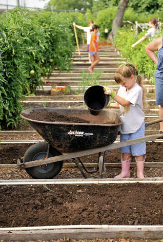 Elizabeth Garner spreads compost in the Children's Garden at the San Antonio Botanical Gardens Saturday morning. The compost came from the city's organic waste program. Photo: Express-News File Photo, FOR THE EXPRESS-NEWS / SAN ANTONIO EXPRESS-NEWS