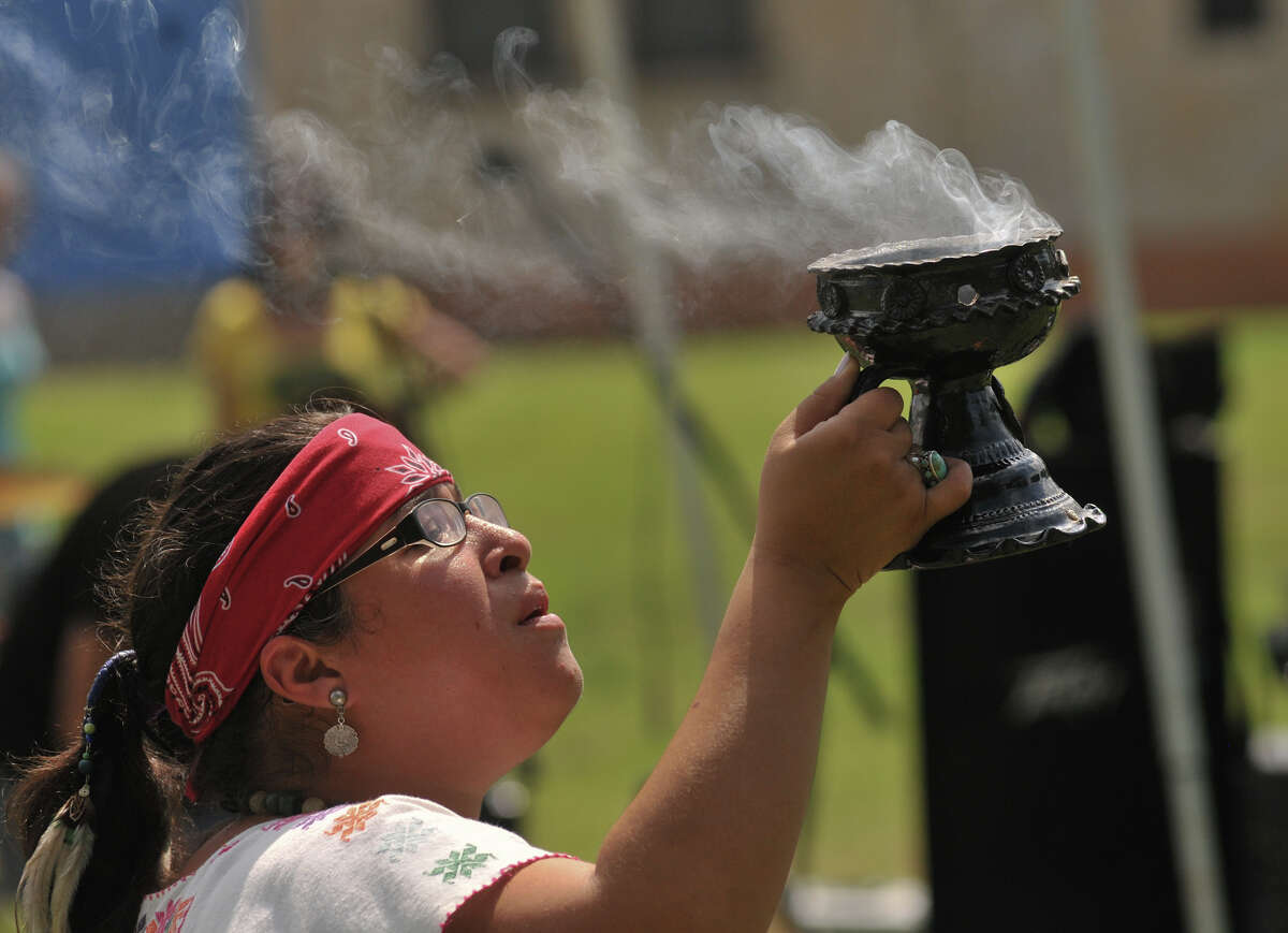 Karla Aguilar uses copal incense for the opening blessing of Girl Zone in Denver Heights Park Saturday. Girl Zone highlights year-long service projects ranging from trash and violence to stray and neglected animals.