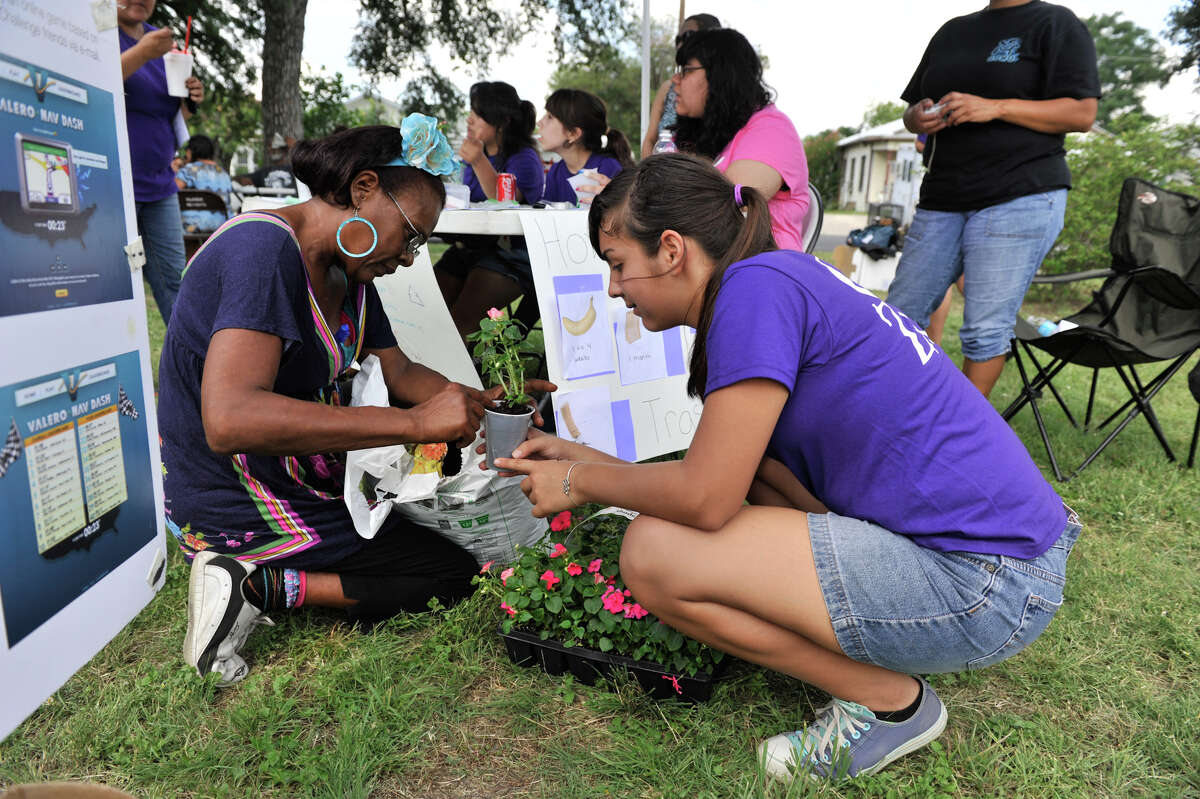 Monica Whittington (left) and Christina Bender use recycleable containers to plant flowers during the Girl Zone event at Denver Heights PArk Saturday. Girl Zone highlights year-long service projects ranging from trash and violence to stray and neglected animals.