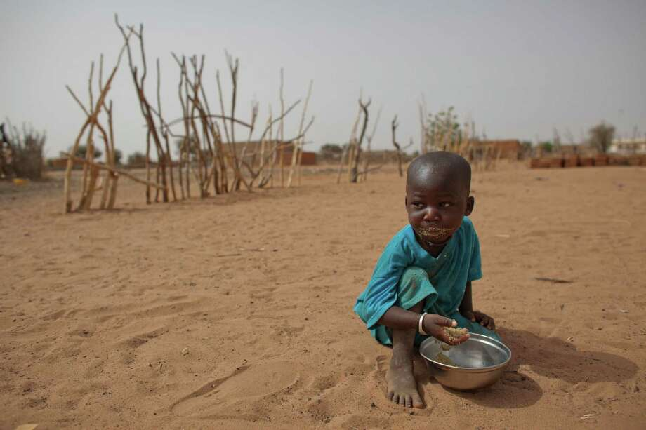 Two-year-old Aliou Seyni Diallo eats dry couscous given to him by a neighbor, after he collapsed in tears of hunger in the village of Goudoude Diobe in Senegal. A wide swath of Africa below the Sahara is at risk of a food shortage. Photo: Rebecca Blackwell / AP