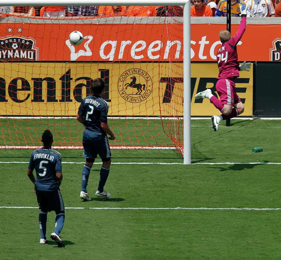 The Los Angeles Galaxy' goalkeeper Brian Perk right, fails to stop the Houston Dynamo's Brian Ching from scoring a goal during the first half of MLS game action at BBVA Compass Stadium Saturday, May 26, 2012, in Houston. Photo: James Nielsen, Chronicle / © Houston Chronicle 2012