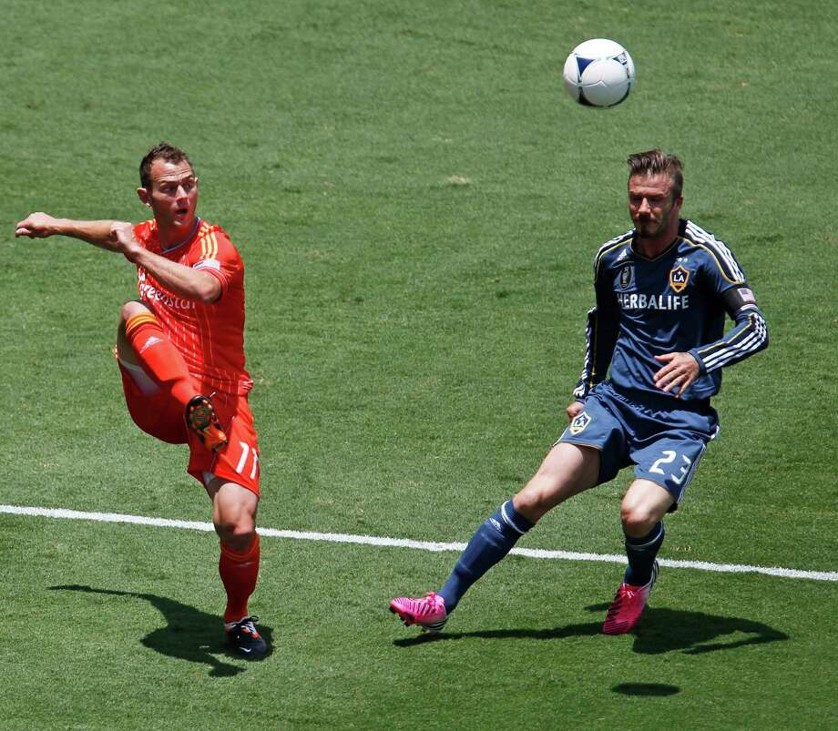The Houston Dynamo's Brad Davis left and Los Angeles Galaxy' David Beckham right during the first half of MLS game action at BBVA Compass Stadium Saturday, May 26, 2012, in Houston. Photo: James Nielsen, Chronicle / © Houston Chronicle 2012