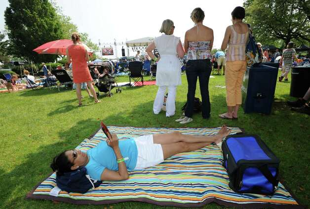 Jasbeena Layman of Greenwich reads on her blanket during the Greenwich Town Party at Roger Sherman Baldwin Park, Saturday, May 26, 2012. Photo: Bob Luckey / Greenwich Time