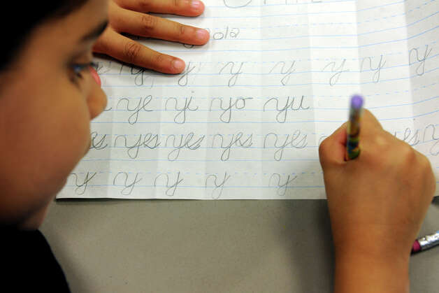 Second grader Jhaishla Ortiz practices her cursive at Waltersville School, in Bridgeport, Conn. April 12th, 2012. Photo: Ned Gerard / Connecticut Post