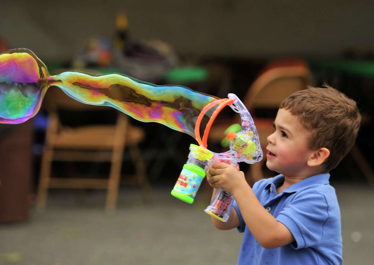 Damien Sanchez, 2, of Danbury, blows bubbles during the Santo Cristo Festival at the Immaculate Heart of Mary Parish in Danbury on Saturday, May 26, 2012.
