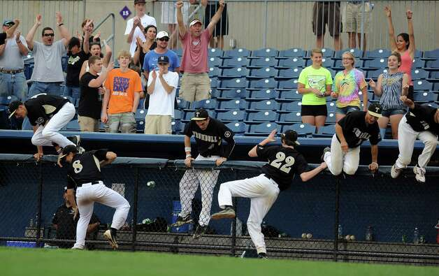 Trumbull players hop over the dugout fence after winning Saturday's FCIAC baseball championship game against Greenwich at the Ballpark at Harbor Yard in Bridgeport on May 26, 2012. Photo: Lindsay Niegelberg / Stamford Advocate
