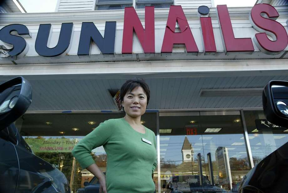 In Milford, Sun Nails owner, Jenny Park smiles outside her nail salon, now reopened after a driver drove through the front entrance on Nov. 12, .Sunday, Nov. 22, 2009. Photo: Phil Noel / Connecticut Post