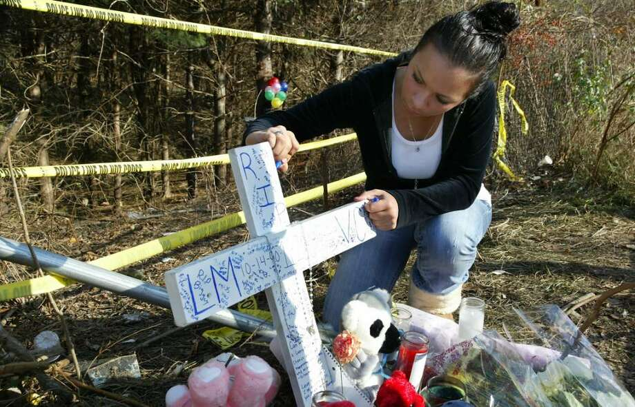 Alana Lorenzo, a Bunnel High School student signs a white wooden cross, one of two memorials set up at the Shelton scene of Friday nights auto accident that took the lives of Larry Morra and Viviana Cavalli, Sunday, Nov. 22, 2009. Photo: Phil Noel / Connecticut Post