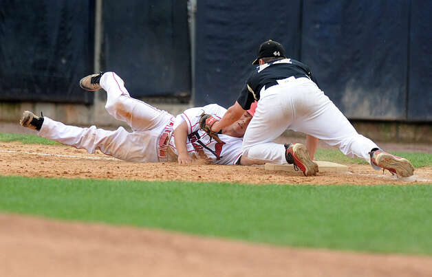 Greenwich's Ricky Okazaki dives back to first base as he id tagged by Trumbull's Carl Johnson during Saturday's FCIAC baseball championship game at the Ballpark at Harbor Yard in Bridgeport on May 26, 2012. Photo: Lindsay Niegelberg / Stamford Advocate
