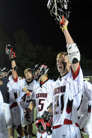 New Canaan's Jack Bratches holds up his helmet after New Canaan came from behind to beat Ridgefield in Friday's FCIAC boys lacrosse championship game at Brien McMahon High School in Norwalk on May 25, 2012. Photo: Lindsay Niegelberg / Stamford Advocate