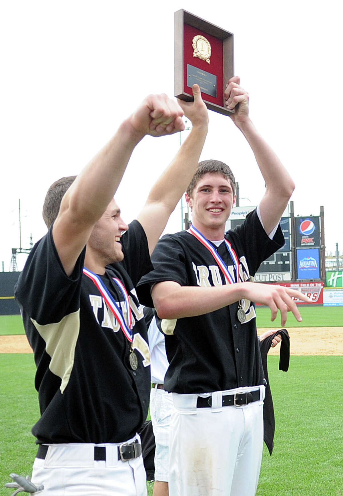 Trumbull's Brendan Moore, left, and Mike Yerina, right, hold up their team's trophy during Saturday's FCIAC baseball championship game at the Ballpark at Harbor Yard in Bridgeport on May 26, 2012.
