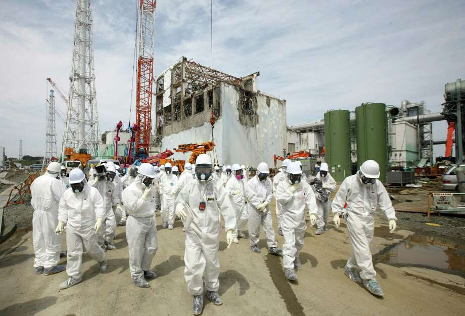 Members of the media and Tokyo Electric Power Co. employees, wearing protective suits and masks, walk past the No. 4 reactor building Saturday while touring the grounds of the Fukushima Daiichi nuclear power plant. Photo: Tomohiro Ohsumi / © 2012 Bloomberg Finance LP