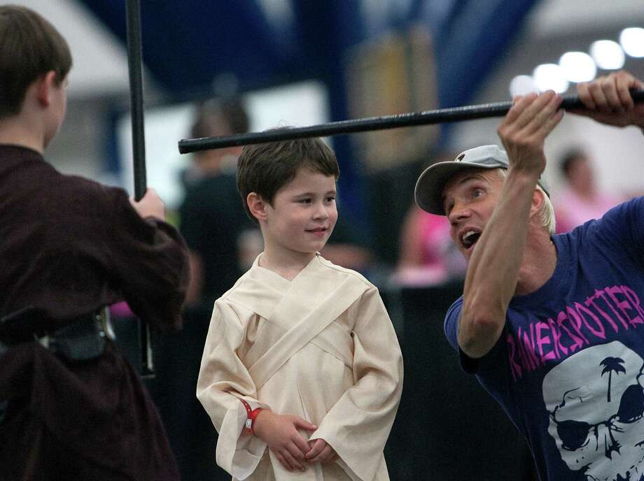 Evan McCoy, 6, left, and Austin McCoy, 4, center, listen as they take Jedi lessons from Nick Gillard, right, at Comicpalooza at the George R. Brown Convention Center Saturday, May 26, 2012, in Houston. Comicapalooza is a multi-format pop culture convention in the southwest region of the United States drawing fans of comics, science fiction, fantasy, video and table-top gaming, anime, music and film. Photo: Cody Duty, Houston Chronicle / © 2011 Houston Chronicle