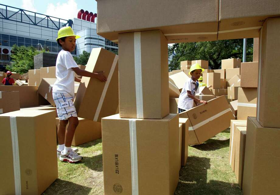 "Caleb Bowser, 10, left, and his brother Jacob Bowser, 6, right, build a structure out of cardboard boxes at ""We Built this City,"" an interactive performance by Australia's Polyglot Theatre, at Discovery Green. Photo: Cody Duty, Houston Chronicle / © 2011 Houston Chronicle"